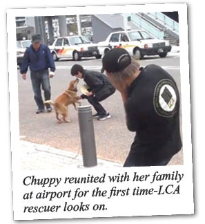 Chuppy reunited with her family at airport for the first time - LCA rescuer looks on.