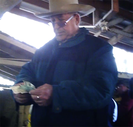 Braulio Hernandez counting cash from sale of pigs